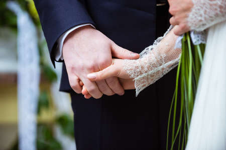 celebration event: Bride and groom holding hands. The groom in a dark suit, the bride in a gown of white lace. Stock Photo