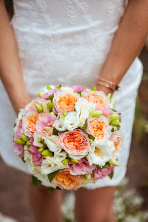 bride in white short dress holding a bouquet of orange roses and white freesias