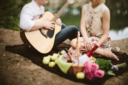 boy lady: man plays the guitar for a girl during a picnic in the park