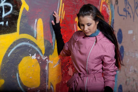 ordeal: Sad girl in a jacket standing near the painted wall. She lowered her head and thinking.
