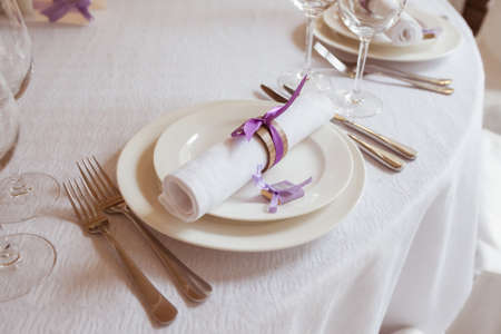 napkin ring: served table in a restaurant, focus on a napkin on the plate