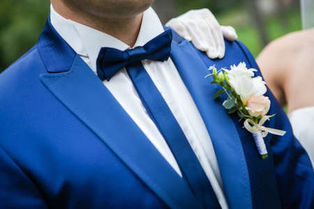 lapel: The groom in a blue suit with a bow tie and buttonhole on the lapel of his jacket. Stock Photo
