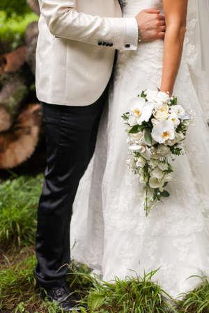 arm bouquet: bride in a white tuxedo hugs the waist bride Stock Photo