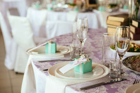 nameplate: Table served with cutlery. on a plate and gift guest nameplate.