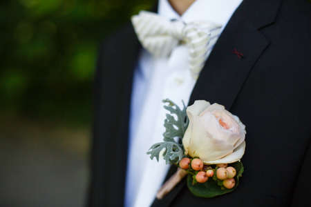 hitched: on his jacket men hitched boutonniere, which consists of cream roses and giperkium