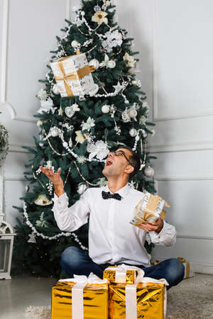 rejoices: man rejoices Christmas gifts. Near Christmas Tree.