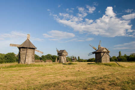 two old wooden windmills with a broken roof on a green field Stock Photo