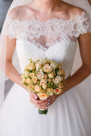 Bride holding a round bouquet of cream roses small Stock Photo