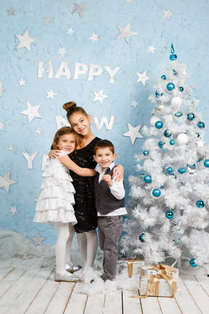 two happy beautiful child near christmas tree