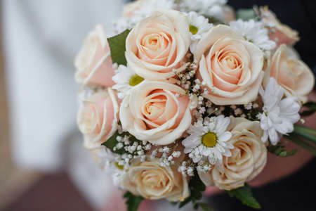 wedding rings lie on a bouquet of yellow and orange roses