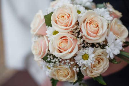 Trauringe liegen auf einem Strauß gelber und oranger Rosen