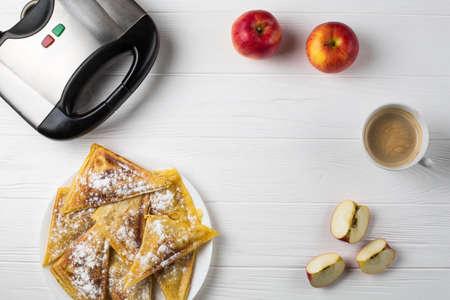 bord met taarten, appels en een elektrische sandwichbroodrooster, vrije plaats