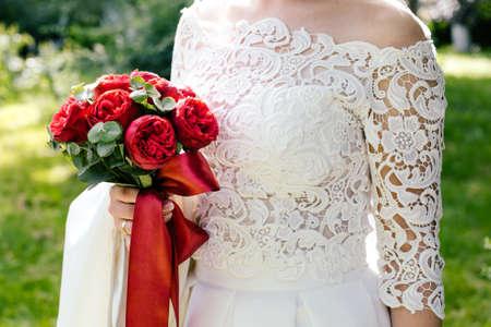 Ramo de boda de rosas de Borgoña en las manos de la novia Foto de archivo - 88930386