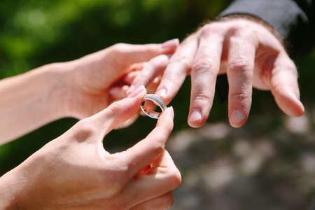 bride puts ring on the grooms hand