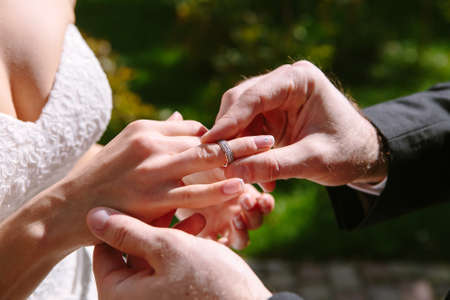 groom puts ring on the brides hand Stock Photo