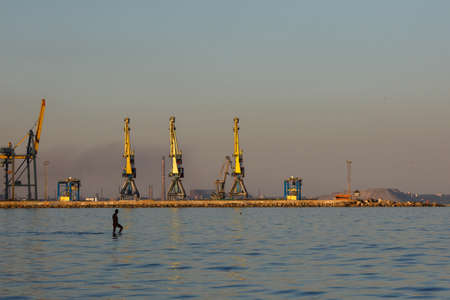 Many big cranes silhouette in the port at golden light of sunset reflected in water. Mariupol, Ukraine. Editorial