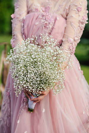 The bride in a pink dress is holding a bouquet of gypsophila