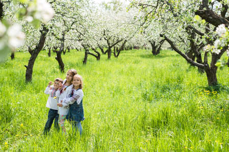 Children in embroidery stand among the flowering garden Stock Photo