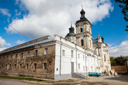 Ancient monastery of Discalced Carmelites, cathedral and fortress wall on background of blue cloudy sky. City Berdychiv, Ukraine. Tourist attraction. Place of visit by Pope John Paul II