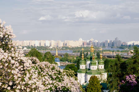 Spring view of Vydubychi Monastery and Dnipro river with lilac blossom in botanical garden in Kyiv, Ukraine