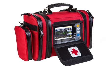 Modern portable biphasic defibrillator in red bag isolated on white