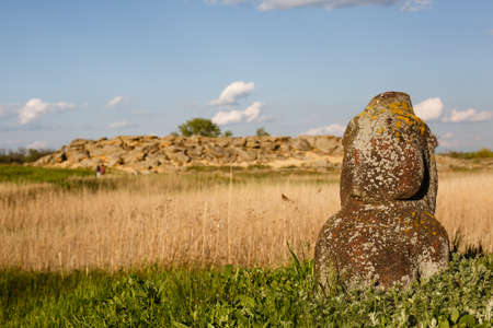 Historical Scythian monuments called kurgan stelae standing in nature against bright green grass, blue sky with clouds Stock Photo