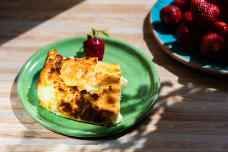Appetizing homemade casserole and strawberries on the table