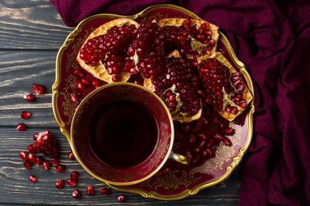 cup with red juice on a table, near a pomegranate and claret cloth