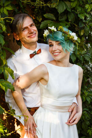 Young wedding couple enjoying romantic moments outside on a summer meadow. The girl has blue hair.