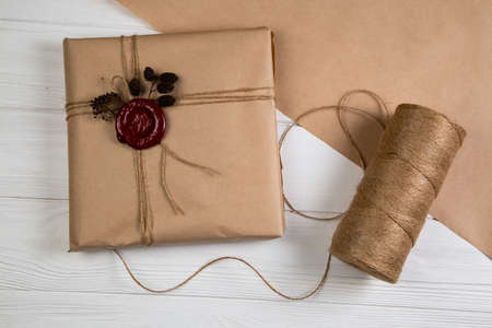 Vintage Christmas gift wrapped in craft paper, tied with string and glued wax seal. Lying on the white wooden table Stok Fotoğraf