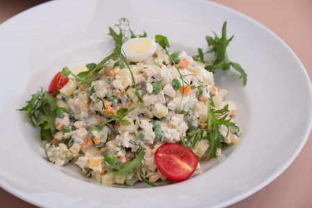 Traditional Russian Christmas Salad Olivier on a white plate with tomatoes