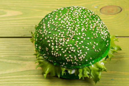 Green burger with lettuce on green wooden background