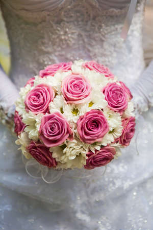 Bride wearing gloves holding a bouquet of roses