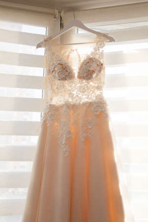 Bright beige wedding dress hanging on a hanger near a window
