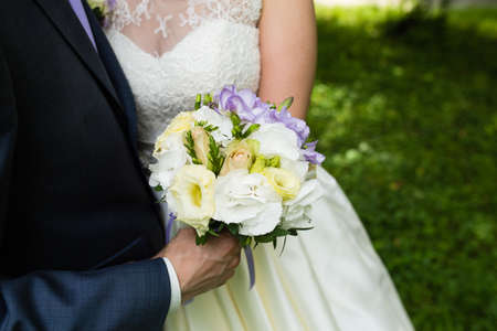 Bride in a long dress holding a bouquet of white and blue flowers
