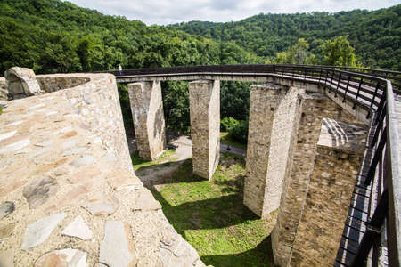 Wooden bridge held by massive rock pillars leads the way into the Neamt Citadel is a medieval fortress located in north-eastern part of Romania, near Targu Neamt, Neamt County. Stock Photo