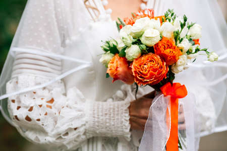 Beautiful autumn wedding bouquet with orange roses in hands of the bride