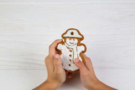 Christmas homemade gingerbread cookies in hands on wooden background Stock Photo