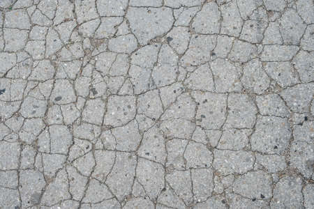 Old road background - surface of grey cracked asphalt texture close up
