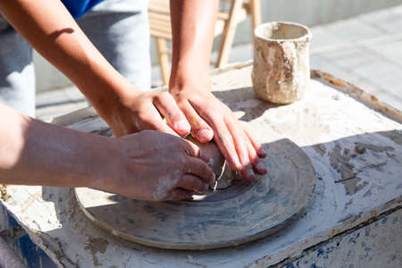 Teaching in masterful studio of ceramics works with clay on a potter's wheel