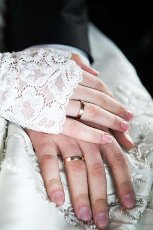 The groom and bride holding hands with wedding rings