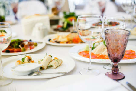 Served for banquet restaurant table with dishes, snack, cutlery, wine and water glasses. Stock Photo