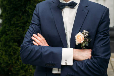 Boutonniere on the lapel of the groom with hands of the groom