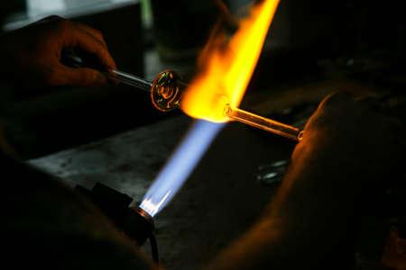 Process glass blowing manufacturing . Fire heats glass blank with glass-blowing burner. Handmade glassworks Standard-Bild