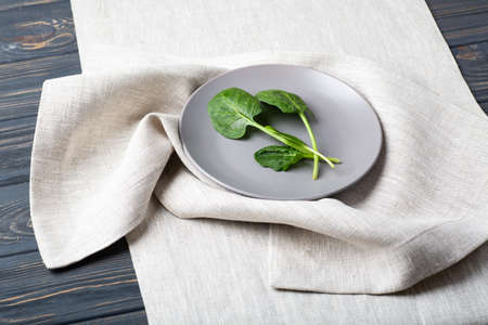 Fresh spinach leaves on a grey plate on a linen tablecloth