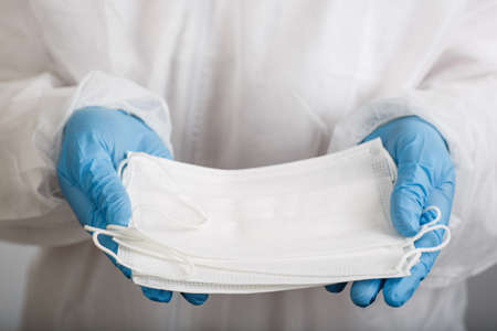 close up of doctor hand with a medical surgical face mask for protection against infection on white background 写真素材