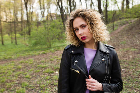 Portrait of a beautiful girl with curly long hair in black leather jacket in the spring forest