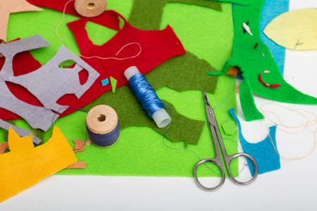 Colored felt, thread, needles and scissors on the white table