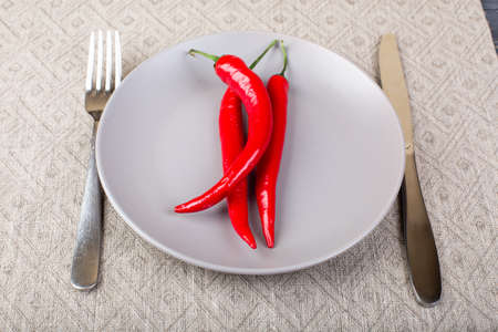 Gray plate with chilli red pepper on , spoon and knife on linen tablecloth top view