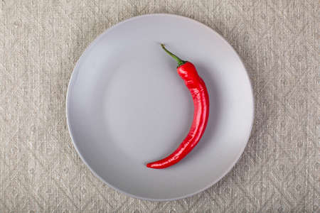 Minimalistic gray plate with chilli red pepper on linen tablecloth top view